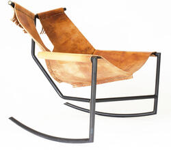 [ee-wah'] chair is a modern rustic rocking chair made from blackened mild steel with brass end plugs and harness leather hand sewn with sinew cord